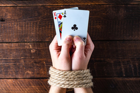 Card addiction. Dependence on poker, gambling. A person with tied hands holding playing cards on a wooden background. Gambling concept