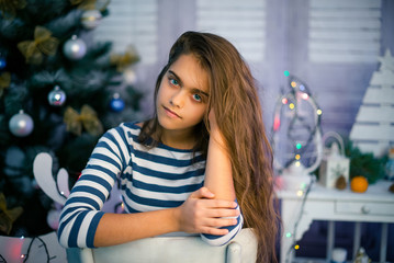 Beautiful girl in Christmas and New year. young girl with long hair sitting on chair. Happy girl in Сhristmas time. girl in background New Year's interior.
