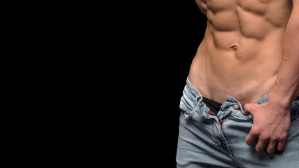 Cropped photo of a sporty man with muscular body in jeans posing in studio