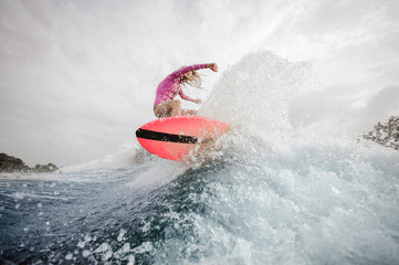 Active teenager girl riding on the orange wakeboard Wall mural