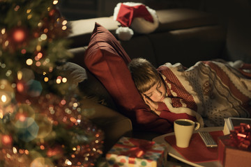 Cute boy waiting for Santa and sleeping on the sofa