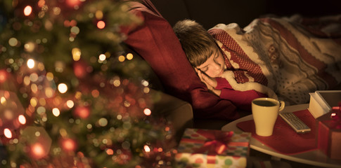 Cute boy sleeping in the living room and waiting for Santa
