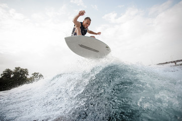 Young active man making jump on the white wakeboard on the blue wave