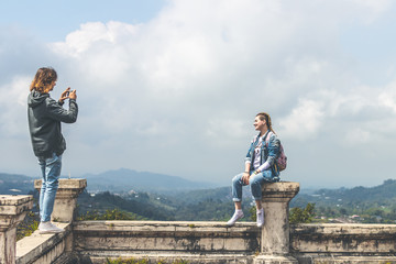Young couple of tourists in abandoned hotel on the north of Bali island, Indonesia. Man making photo of his girlfriend.