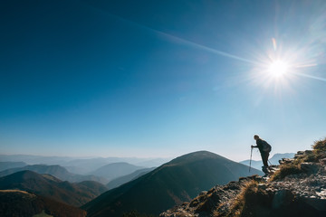 Backpacker hiker on the mountain hill in contrast sun light