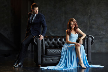 Young businessman in a business suit and a beautiful young brunette in a long blue dress