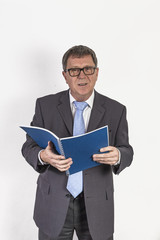 succesful business man with blue tie reading in a journal