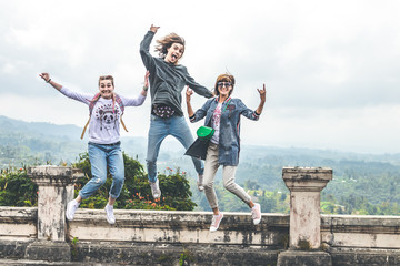 Three young tourists jumping in abandoned hotel on the north of Bali island, Indonesia.