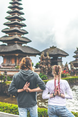 Young romantic couple of trourists on the Ulan Danu temple background. Bali island.