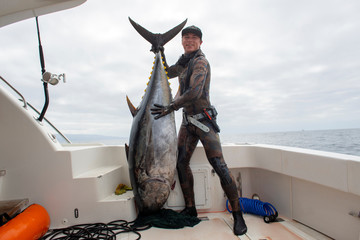 Ryder Devoe,19, proudly shows off his 200-pound Pacific bluefin tuna after free diving to spear the fish off the coast of San Diego