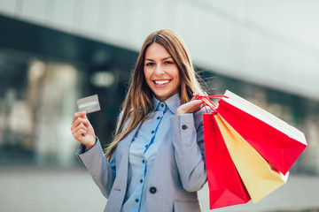 Woman in shopping. Happy woman with shopping bags and credit card enjoying in shopping.