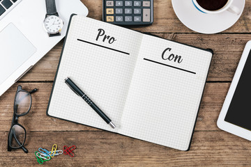 Pro and Con lists in note pad on office flat lay