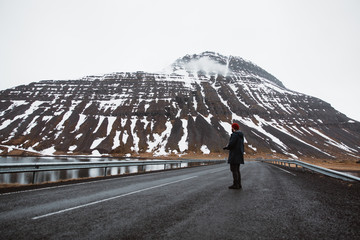 Traveler on empty cold road with cliffs