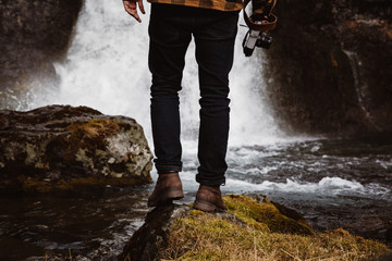 Anonymous tourist with camera against waterfall