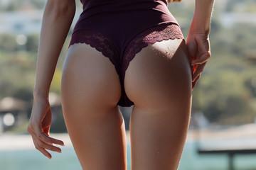 Crop woman in swimwear touching buttocks