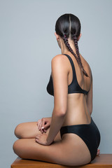 Young woman with pigtails wearing black lingerie sitting, back view.