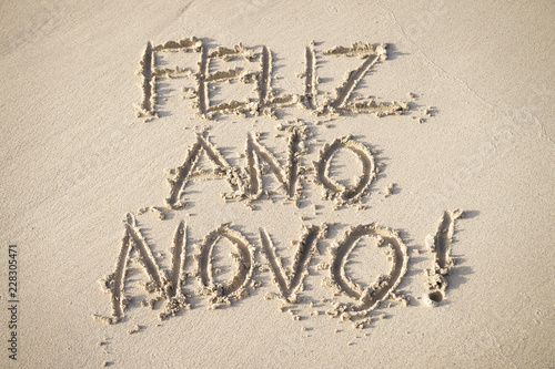 feliz ano novo message happy new year in portuguese handwritten on the smooth sand