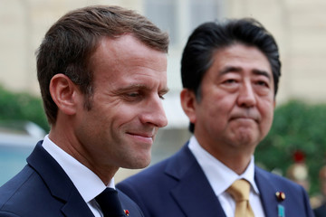 French President Emmanuel Macron and Japanese Prime Minister Shinzo Abe speak to the media in the courtyard of the Elysee Palace in Paris