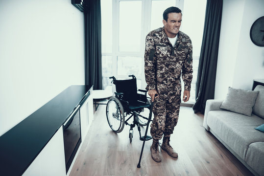 Disabled Soldier Leans on Crutch near Wheelchair