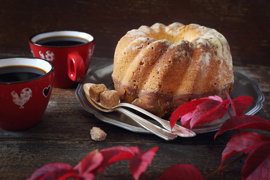 Homemade Kouglof cake, two cups of coffee and autumn red leaves.