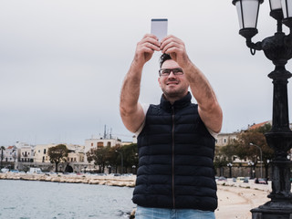 Stylish, happy man with a phone on the background of a sea bay and coastline on a cloudy day