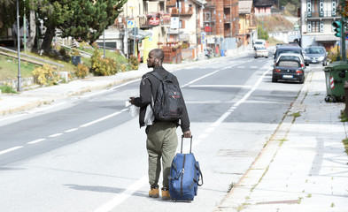 A migrant walks along the road next to the French border in Claviere