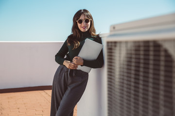 Businesswoman with sunglasses standing on rooftop, holding laptop