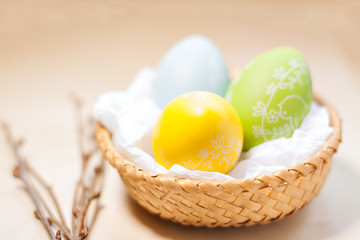 Colored easter eggs in nest on rustic wooden planks with branch