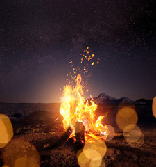 Watching the stars around a glowing warm campfire at night. Photo composite.