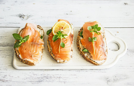 Sandwiches with Salmon and Lemon on a Tree Background