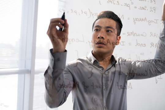 Young Asian man writing script on glass transparent board standing behind it