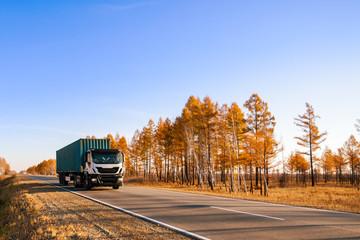 White semi-truck on autumn road