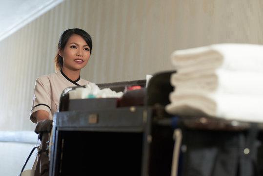 Young Asian woman in uniform walking and pushing maid cart in hotel corridor