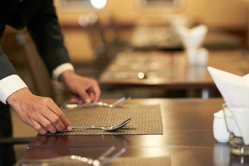Crop elegant hotel waiter arranging silverware on napkin on table in restaurant