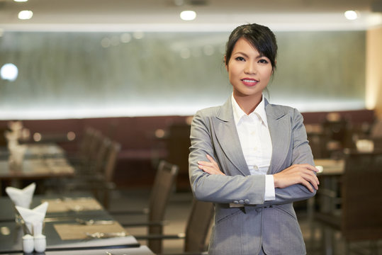 Smiling elegant Asian woman in suit working as hostess in hotel restaurant looking at camera