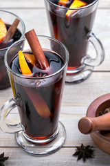 Hot mulled wine with spices and orange on wood background. Vertical picture