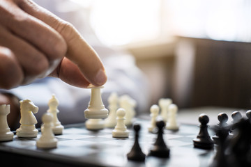 Hands of confident businessman colleagues playing chess game to development analysis new strategy plan, leader and teamwork concept for win and success