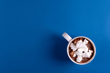 Hot chocolate with marshmallow candies on blue paper background. Top view. Copy space
