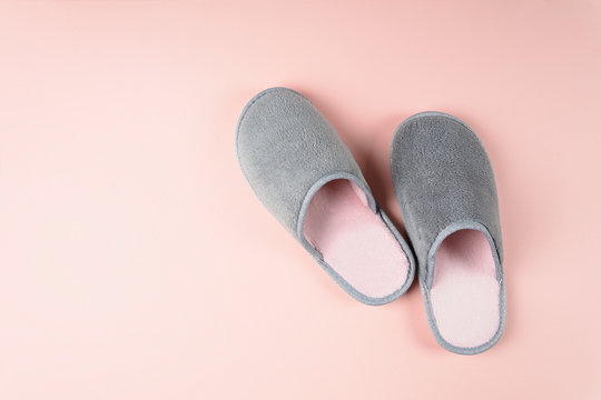 Gray and pink home slippers on a pastel paper background. Top view. Copy space