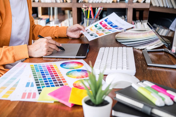Image of female creative graphic designer working on color selection and drawing on graphics tablet at workplace with work tools and accessories