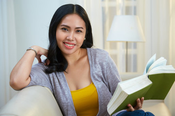 Pretty Filipino lady smiling and looking at camera while sitting on comfortable couch in cozy living room and reading interesting book