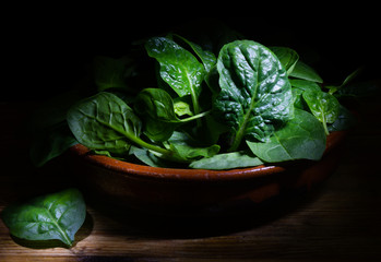 Fresh spinach leaves on rustic background