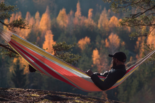 A man sits in a hammock and admires the autumn forest