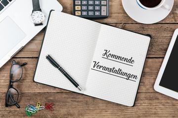 Kommende Veranstaltungen geschrieben in Heft auf Büro Flat Lay Schreibtisch