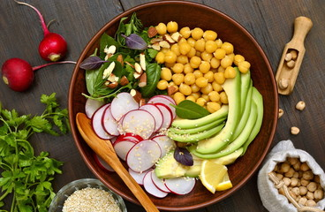 Vegetarian bowl with chickpeas, radish, avocado, herb and seeds,  salad, top view