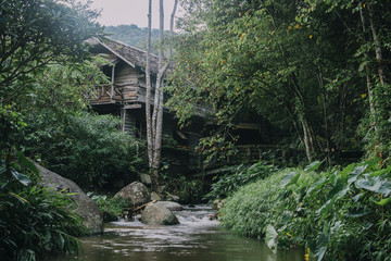 Resting place with waterfall, emerald green water and old wooden house in the mist morning
