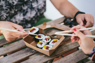 Crop friends eating sushi from box