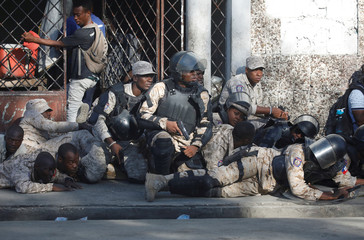 Haitian National Police officers take cover during a shooting after a ceremony for the anniversary of the killing of Jean-Jacques Dessalines in Port-au-Prince