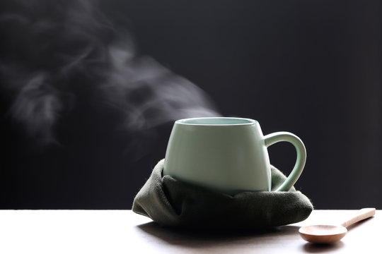 Selective focus of smoke rising with hot soup in cup and spoon on dark background