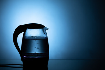 electric glass tea kettle on blue background